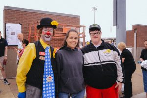 Photo of a woman standing with a clown and a young man with downs syndrome