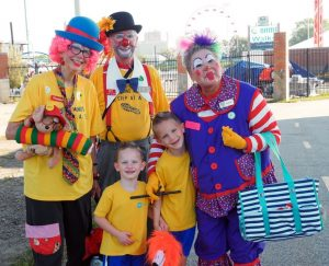 Group of people dressed up as clowns with two boys standing in front