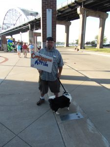 "Man holding a sign that says ""Where Compassion Meets Action"""