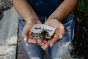 A person holding change and a piece of paper that says 'Make A Change'