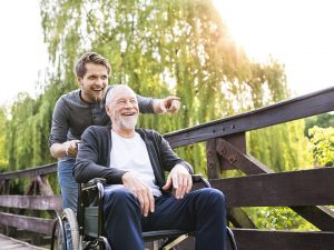 Son pushing grandfather in wheelchair