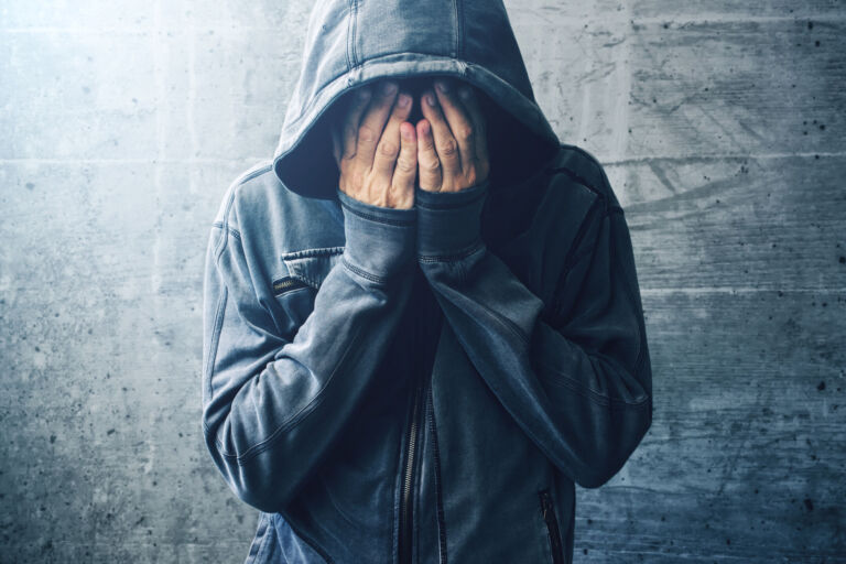 White man holding hands over his face wearing a hoodie.